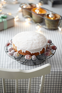 Iced cake on table with decorative lightsの写真素材 [FYI03604671]