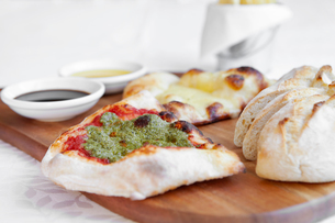 Fresh pizza bread with dipping sauces on chopping boardの写真素材 [FYI03604674]
