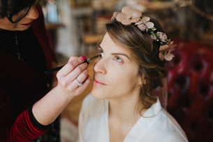 Bride preparing for wedding with make-up artistの写真素材 [FYI03604740]
