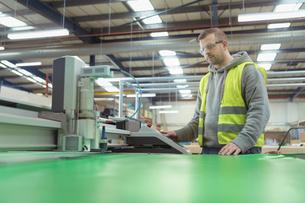 Worker operating vinyl cutting machine in factoryの写真素材 [FYI03604908]