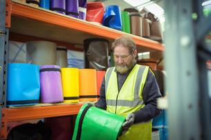 Worker selecting coloured vinyl rolls in factoryの写真素材 [FYI03604914]