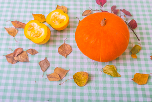 Still life of pumpkin and chopped pumpkin with autumn leaves, close-upの写真素材 [FYI03604978]