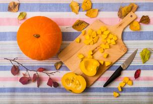 Still life of pumpkin, chopping board and chopped pumpkin, overhead viewの写真素材 [FYI03604980]