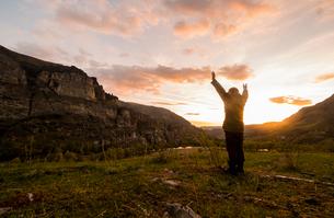 Man standing in rural setting, arms raised towards sunの写真素材 [FYI03604998]