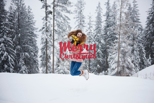 Young woman jumping with Merry Christmas words in snowの写真素材 [FYI03605067]