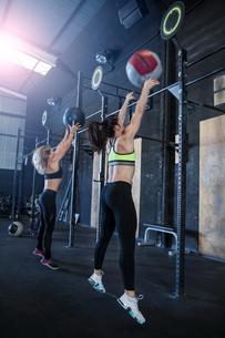 Two women exercising in gym, using medicine ballsの写真素材 [FYI03605093]