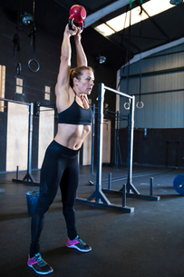 Woman exercising in gymnasium, using kettlebellの写真素材 [FYI03605103]