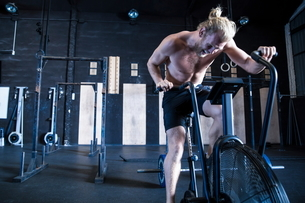 Man exercising in gymnasium, using air resistance exercise bikeの写真素材 [FYI03605107]
