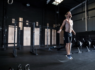 Man exercising in gymnasium, skipping with speed ropeの写真素材 [FYI03605128]