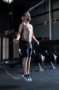 Man exercising in gymnasium, skipping with speed ropeの写真素材 [FYI03605129]