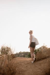 Woman walking along rural pathway, rear view, Tossa de mar, Catalonia, Spainの写真素材 [FYI03605140]