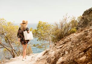 Woman walking along coastal pathway, rear view, Tossa de mar, Catalonia, Spainの写真素材 [FYI03605148]