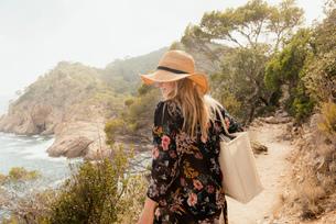 Woman walking along coastal pathway, rear view, Tossa de mar, Catalonia, Spainの写真素材 [FYI03605149]