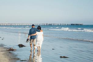 Couple walking along beach, barefoot, rear view, Seal Beach, California, USAの写真素材 [FYI03605180]