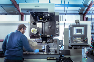 Engineer operating a wire erosion machine in precision engineering factoryの写真素材 [FYI03605200]