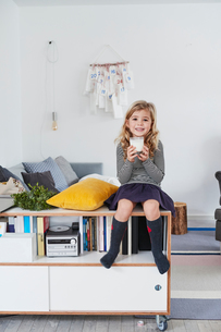 Young girl sitting in living room, holding glass of milkの写真素材 [FYI03605228]