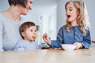 Family sitting at kitchen table, young girl spoon-feeding baby sisterの写真素材 [FYI03605235]
