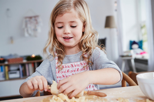 Young girl rolling out cookie dough, dough stuck to rolling pinの写真素材 [FYI03605239]