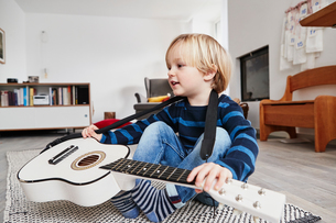 Young boy sitting with guitar around neckの写真素材 [FYI03605265]