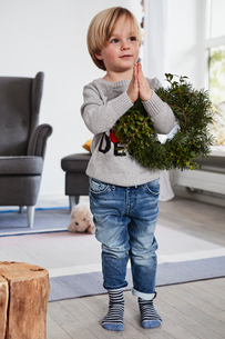 Young boy standing with hands together, holding wreath over armの写真素材 [FYI03605270]