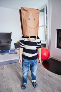 Portrait of young boy with brown bag on head, drawn face on brown bagの写真素材 [FYI03605274]