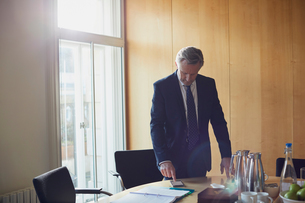 Businessman looking at smartphone on boardroom tableの写真素材 [FYI03605312]