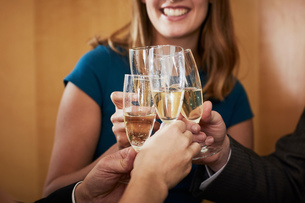 Business team raising champagne toast at office celebration, croppedの写真素材 [FYI03605320]