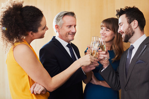Business team raising champagne toast at office celebrationの写真素材 [FYI03605322]