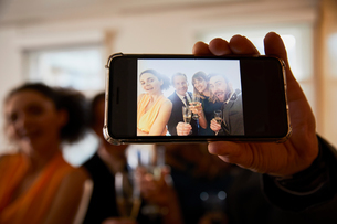 Business team raising champagne toast at office celebration, smartphone selfie close upの写真素材 [FYI03605324]