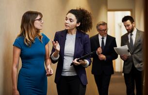 Business team walking and talking along office corridorの写真素材 [FYI03605334]