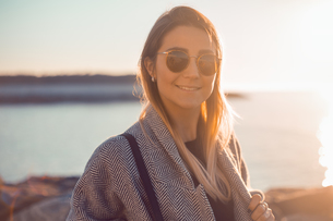 Portrait of woman wearing sunglasses looking at camera smilingの写真素材 [FYI03605419]