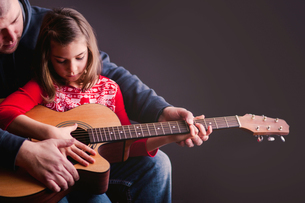 Father teaching daughter to play guitarの写真素材 [FYI03605421]