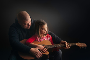 Father teaching daughter to play guitarの写真素材 [FYI03605423]