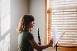 Girl at clarinet practice by windowの写真素材 [FYI03605429]