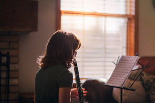 Girl at clarinet practice by windowの写真素材 [FYI03605431]