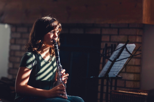 Girl at clarinet practice by fireplaceの写真素材 [FYI03605432]