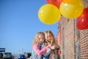 Two sisters with bunch of colourful balloons, portraitの写真素材 [FYI03605464]