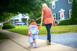 Mid adult woman walking with daughter on suburban sidewalk, rear viewの写真素材 [FYI03605476]