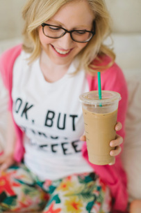 Young woman at home with cup of takeaway coffeeの写真素材 [FYI03605498]