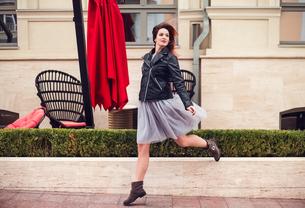 Portrait of woman skipping in streetの写真素材 [FYI03605554]