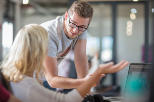 Male and female colleagues talking at office deskの写真素材 [FYI03605709]