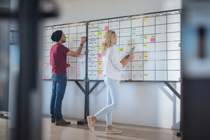Male and female colleague planning  ideas on office whiteboardの写真素材 [FYI03605711]