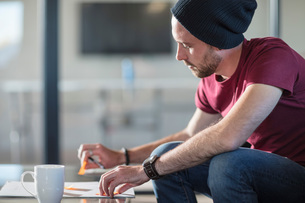 Young man making notes during coffee break in officeの写真素材 [FYI03605719]