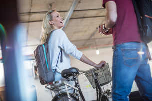 Young woman with bicycle greeting colleague in officeの写真素材 [FYI03605721]