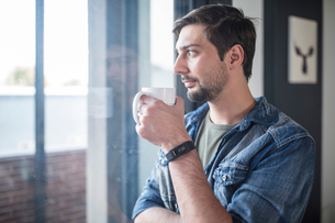 Young man drinking coffee while looking out of  office windowの写真素材 [FYI03605724]