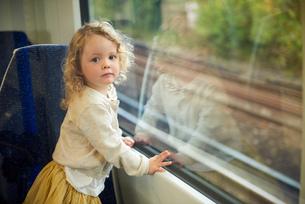 Female toddler on train, portraitの写真素材 [FYI03605822]