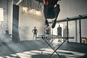 Man in mid air jumping hurdles in gymの写真素材 [FYI03606038]