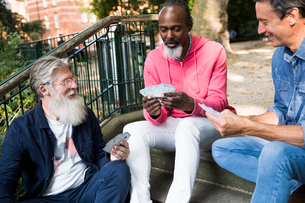 Three mature men, outdoors, sitting on steps, playing cardsの写真素材 [FYI03606116]