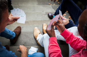 Three mature men, outdoors, sitting on steps, playing cards, elevated viewの写真素材 [FYI03606120]