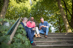 Three mature men, outdoors, sitting on steps, playing cards, low angle viewの写真素材 [FYI03606121]